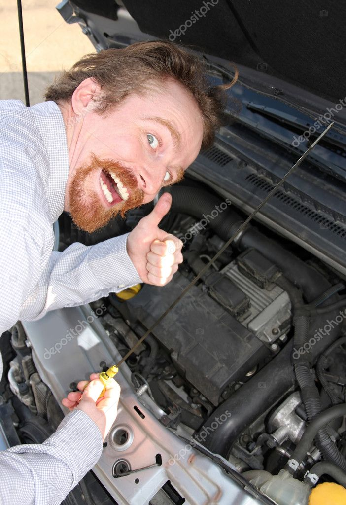 Happy man checking engine oil dipstick in car — Stock Photo #1693037