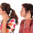 Two woman putting hearing aid into ear - Lizenzfreies Foto