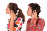 Two woman putting hearing aid into ear — Stock Photo