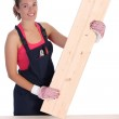 Woman carpenter holding wooden plank — Stock Photo #1910779