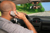 Driver and mobil phone — Stock Photo