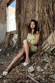 La ragazza si siede ad una parete di casa — Foto Stock