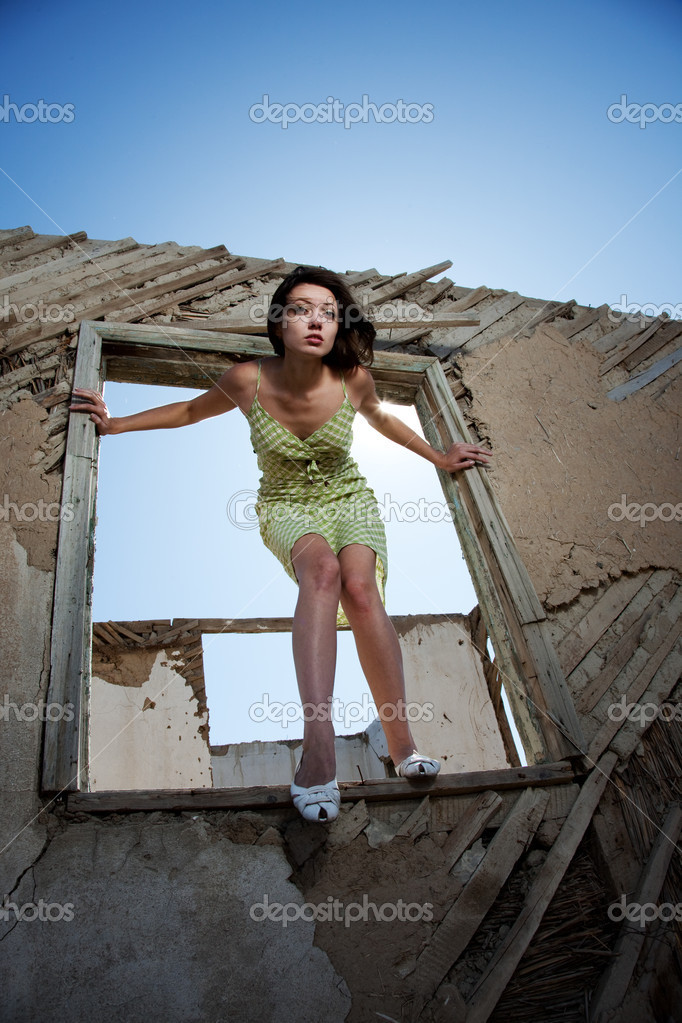 The girl costs at a window looks forward and the sun shines — Stock Photo #1666502