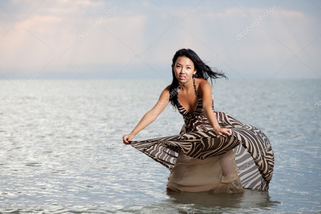 Asian beauty girl stay on the beach in water, play with dress  Stock Photo #1719700