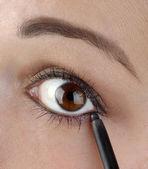 Młode kobiety za pomocą ołówkiem eyeliner — Zdjęcie stockowe