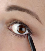 Young women using an eyeliner pencil — Stok fotoğraf