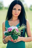 Beautiful young woman with bouquet — Stock Photo