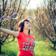 Beautiful model blowing bubbles — Stock fotografie