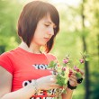 Pretty woman holding spring flowers — Stock Photo