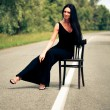 Woman sits on a chair on the road — Stok fotoğraf