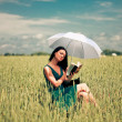 Girl with book under an umbrella — Stock Photo #1809705