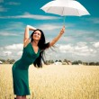 Girl with umbrellin field — Foto de stock #1809803