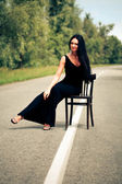 Woman sits on a chair on the road — Stock Photo