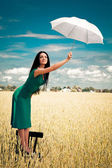 Girl with an umbrella in the field — Stock Photo