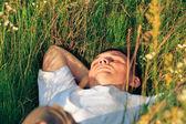 Mladý dospělý muž v jarní tráva — Stock fotografie