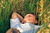 Young adult man in spring grass — Stok fotoğraf