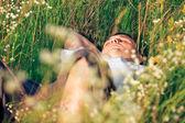 молодой взрослый человек в траве весной — Стоковое фото