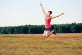 Happy woman jumping in yellow field — Stockfoto