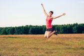 Femme heureuse sautant dans le champ jaune — Photo