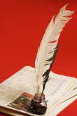 Feather quill and newspapers — Stock Photo