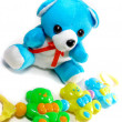 Cute teddy bear and rattle - Stock Photo