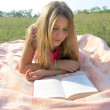 Teenage girl reading a book outdoor — Stock Photo