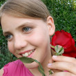 Stock Photo: Happy girl with a red rose