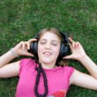 Girl listening music on the grass — Stock Photo