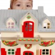 Stock Photo: Little girl protruding behind toy house