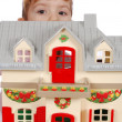 Little girl protruding behind toy house — Stock Photo