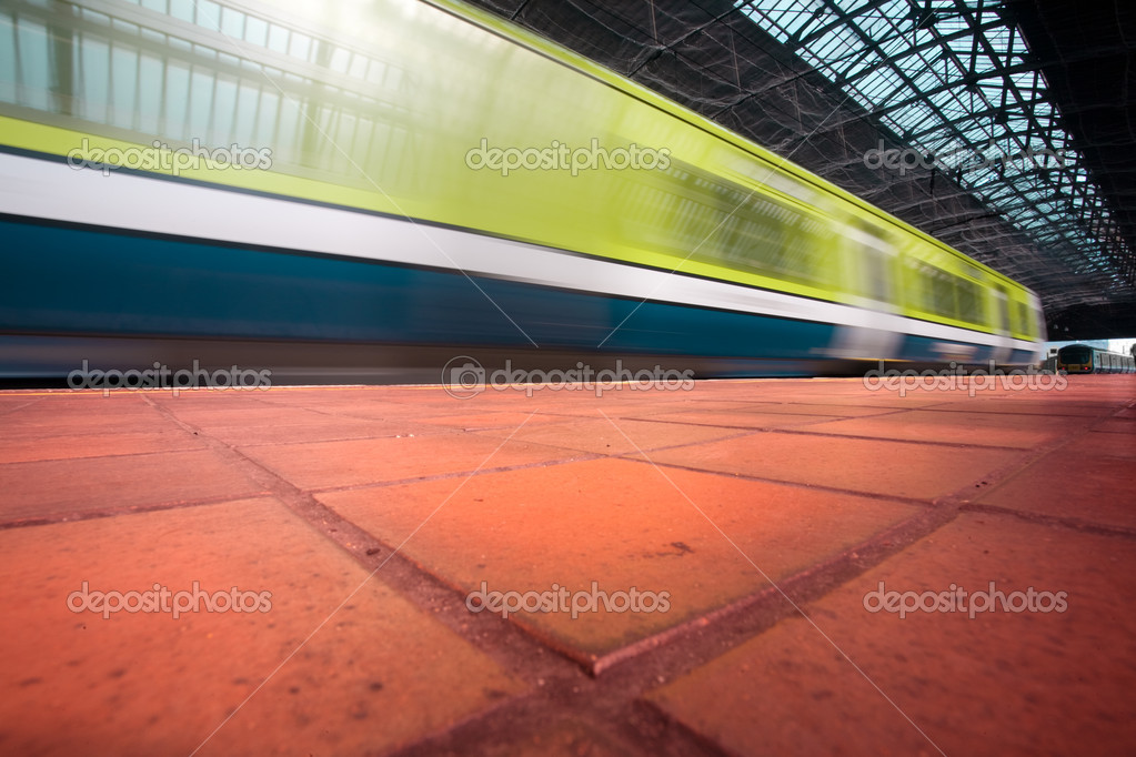 Commuter train in motion blur enters the city station — Stock Photo #1680068