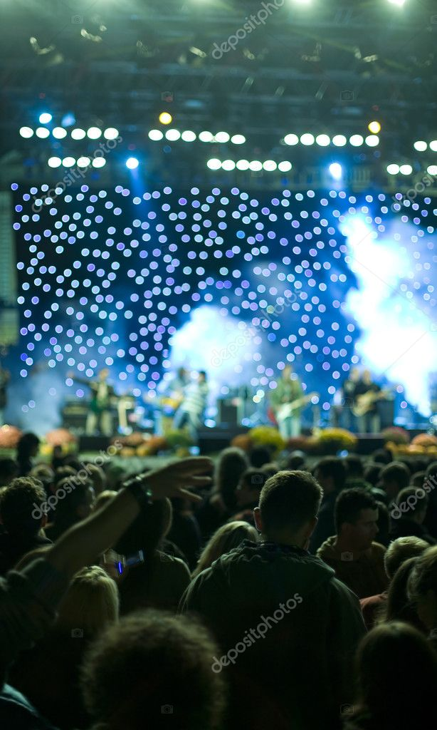 Band at a rock concert.Concert stage lights out of focus and crowd in blur — Stock Photo #1703917