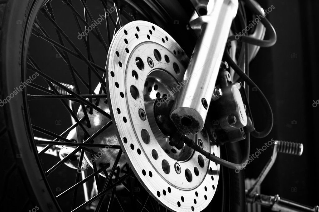 Closeup detail of a motorcycle front wheel with black spikes and brake disc — Stock Photo #1711766