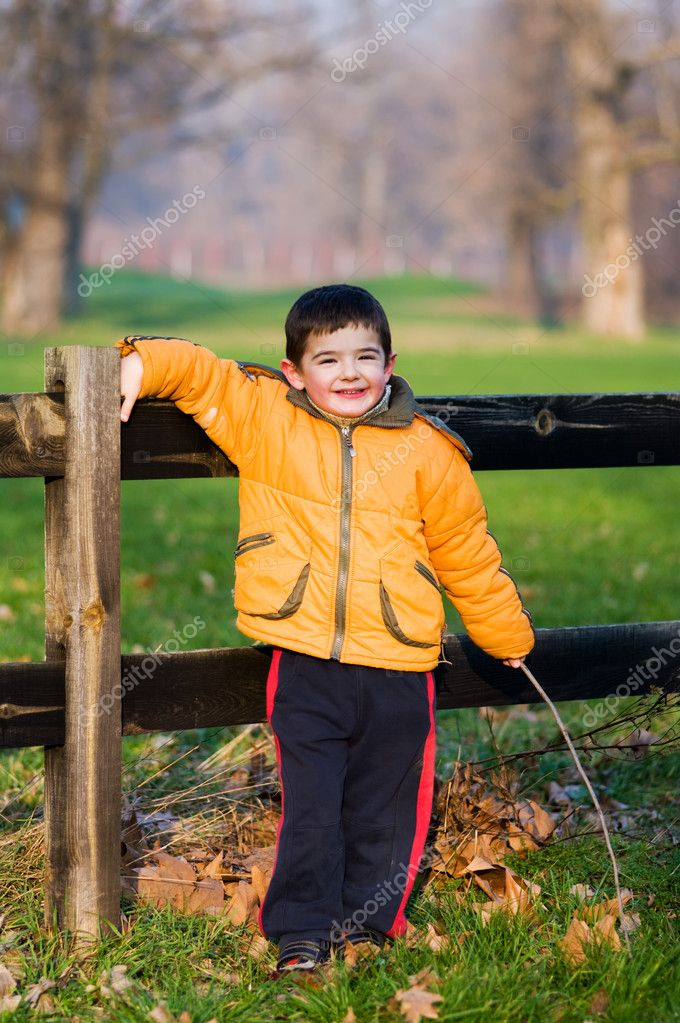 Young boy standing near old fence. — Stock Photo #1663664
