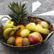 Fruit basket at garden table - Stock Photo