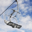 Empty chairlift on blue sky with clouds — Stock Photo