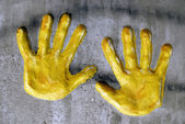 Yellow hands in gray asphalt — Stock Photo
