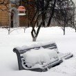 Snow covered bench - Stock Photo
