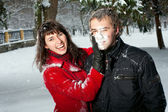 Beautiful couple playing in snow — Stock Photo