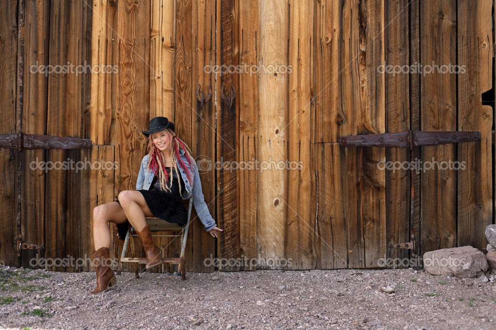 Young woman in Cowgirl style clothing sitting outside an old timber barn  Stock Photo #1711970