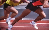 Detail views of male athletes running on synthetic running track — Stock Photo