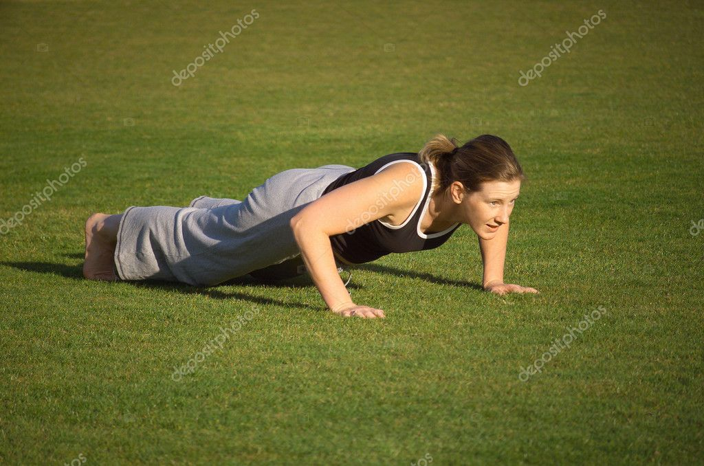 Female exercising in the park, doing push ups, half way point — Stock Photo #1785702