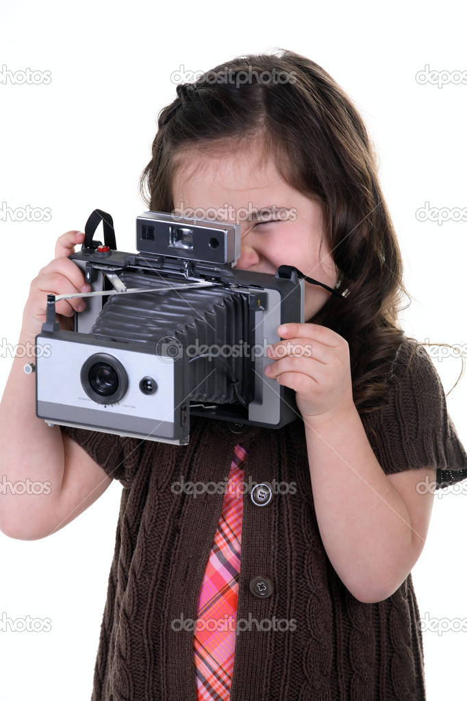 Very cute young girl holding a very old film camera and playing at being a photographer — Stock Photo #1815667