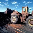 Front End Loader moving ore stockpile — Stock Photo