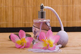 Kwiat i szklane butelki perfum — Zdjęcie stockowe