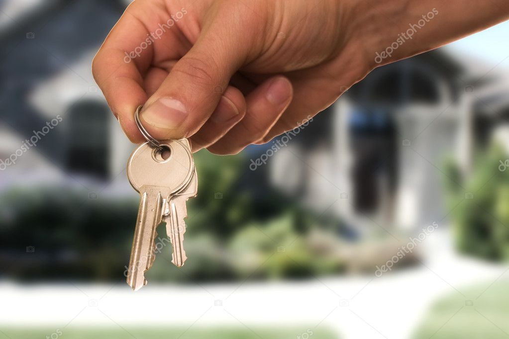 Hand holding keys, house in the background — Stock Photo #1705511