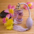 Flower and glass perfume bottle — Stock Photo
