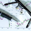 Fountain pen and glasses on stock chart. — Stock Photo