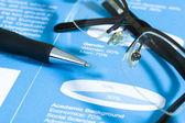Penna stilografica e occhiali sul grafico azionario. — Foto Stock