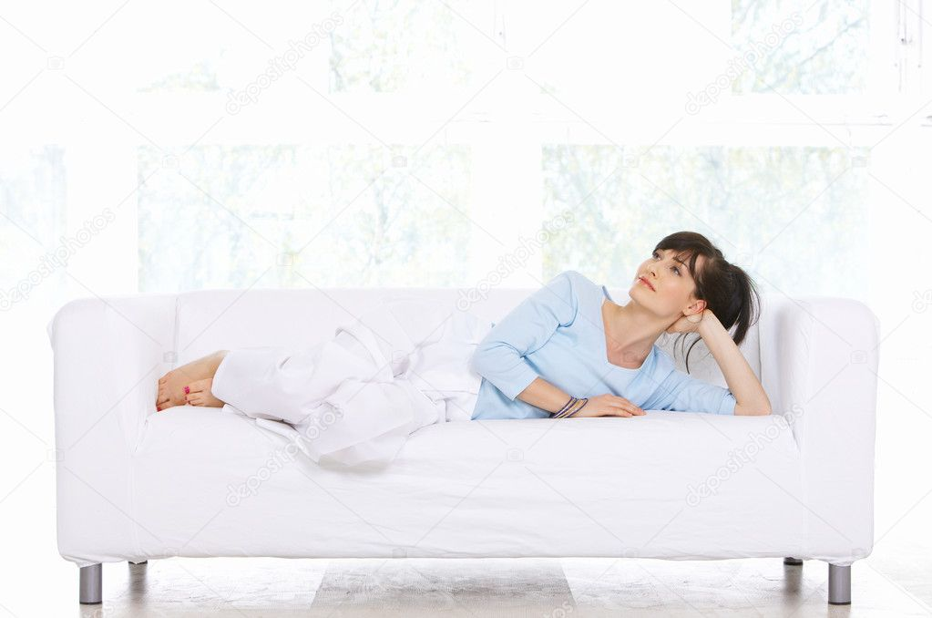 Young woman relaxing on couch in her home — Stock Photo #1929592